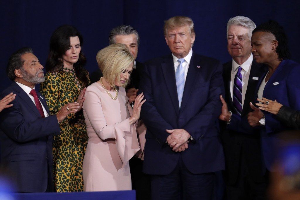 FILE - In this Jan. 3, 2020, file photo, faith leaders pray with President Donald Trump during a rally for evangelical supporters at the King Jesus In...