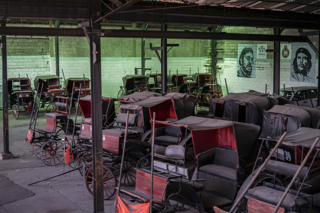 Horse carts used to give rides to tourists sit idle in the garage of a cooperative where murals of the late leader Fidel Castro and Revolutionary hero...