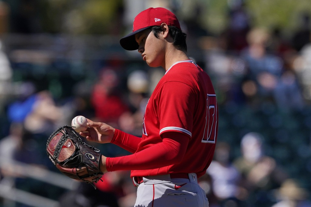 Los Angeles Angels pitcher Shohei Ohtani looks at the baseball after a pitch against the Oakland Athletics during the first inning of a spring trainin...