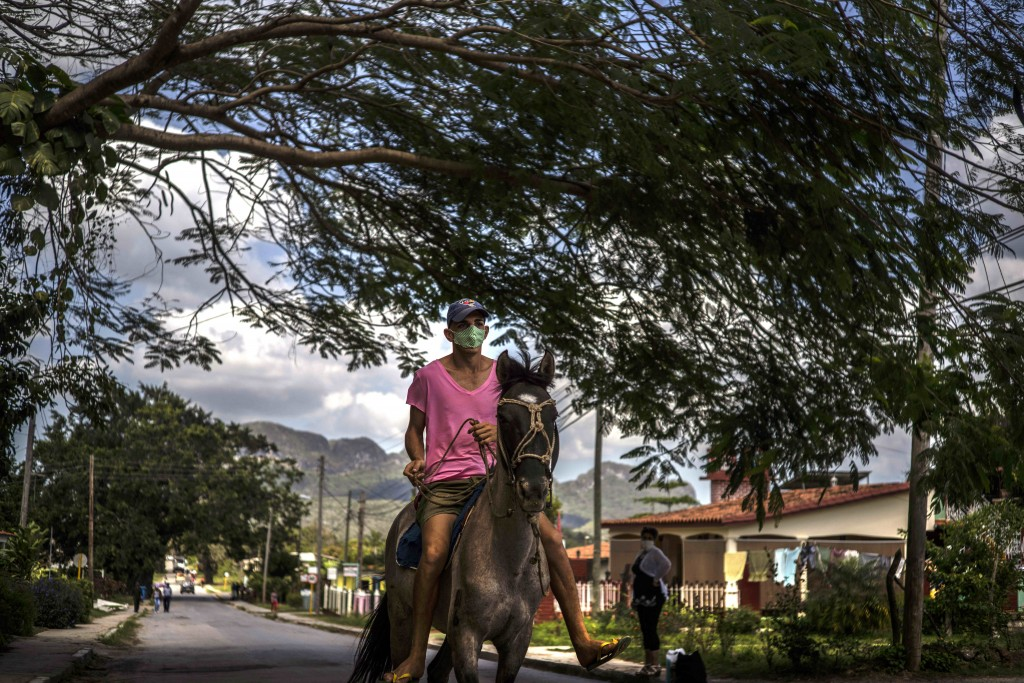 A man rides his horse through Viñales, Cuba, March 1, 2021. Both U.S. sanctions meant to punish the government and a COVID-19 pandemic have squashed t...