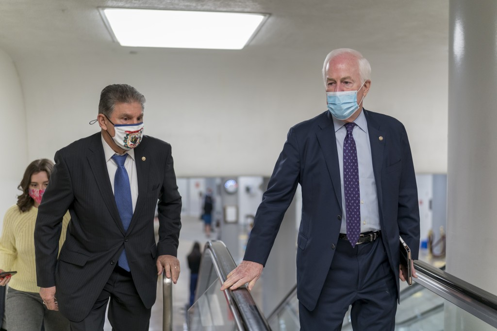 Sen. Joe Manchin, D-W.Va., left, and Sen. John Cornyn, R-Texas, head to the chamber as the Senate steers toward a voting marathon on the Democrats' $1...
