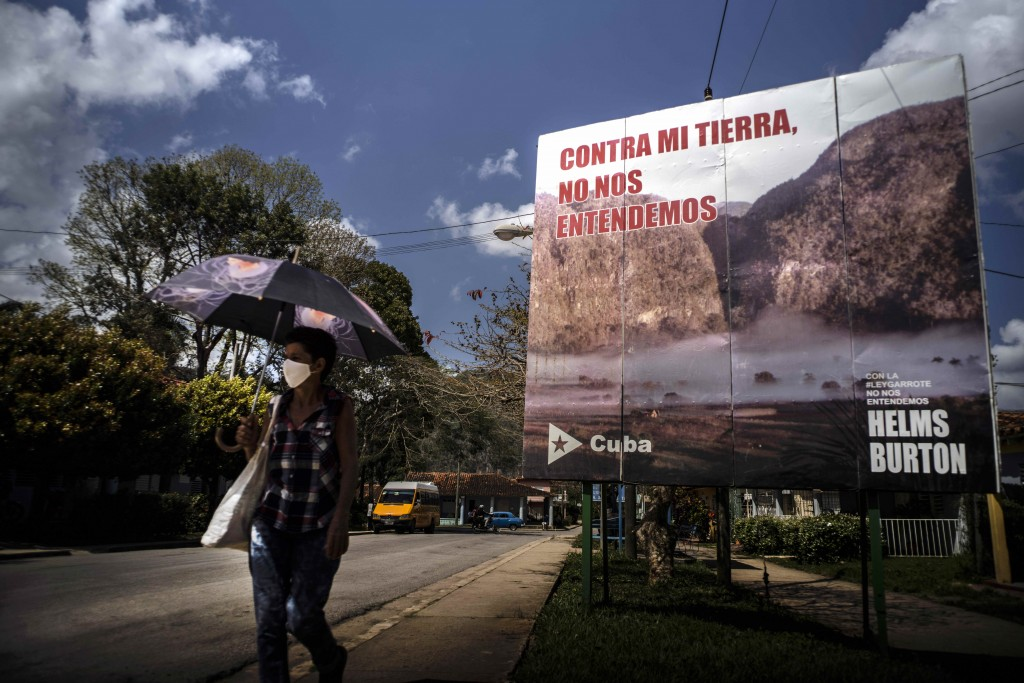 """A woman walks past an anti-embargo sign that reads in Spanish: """"Against my land, we don't understand each other"""" in Viñales, Cuba, March 1, 2021. Both..."""
