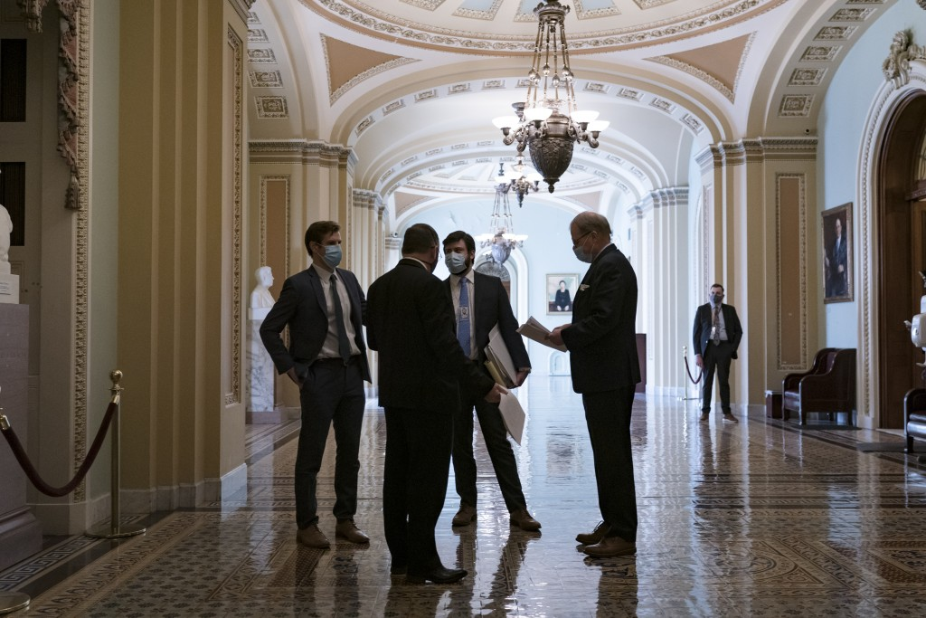 Congressional staffers wait in the ornate corridor outside the Senate chamber during a delay in work on the Democrats' $1.9 trillion COVID-19 relief b...