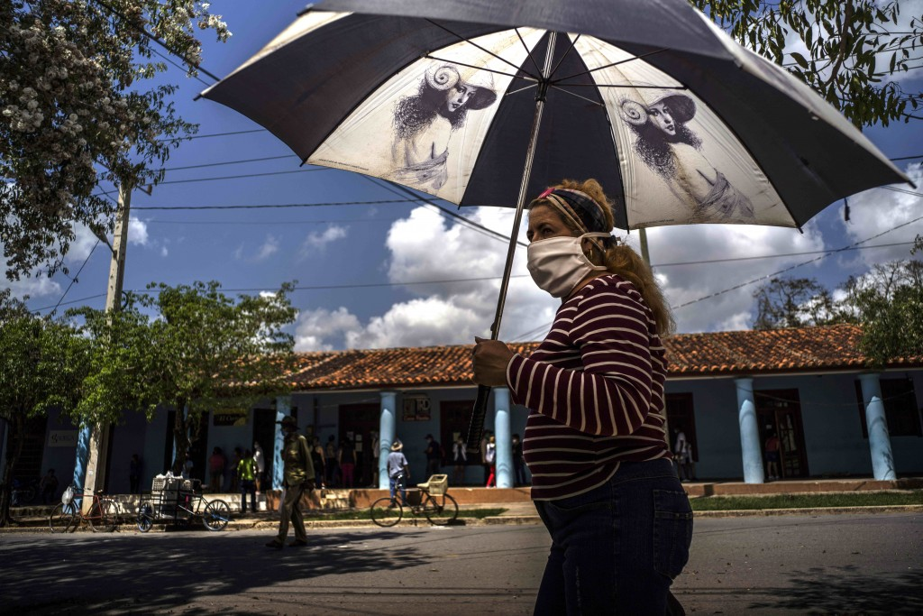 A woman wearing a mask amid the COVID-19 pandemic shades herself under the strong midday sun in Viñales, Cuba, March 1, 2021. Some Cubans are living o...