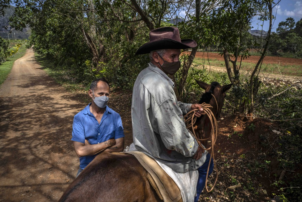 Luis Orlando Deulofeu, who owns the MogoteArt Hostel, poses for a portrait behind a passing horse rider outside his hotel in Viñales, Cuba, March 1, 2...