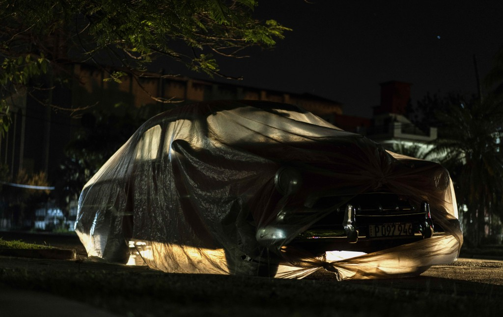 A classic American car is wrapped in plastic to prevent sea salt from corroding it in Havana, Cuba, Tuesday, March 2, 2021. Vintage cars in Cuba are p...