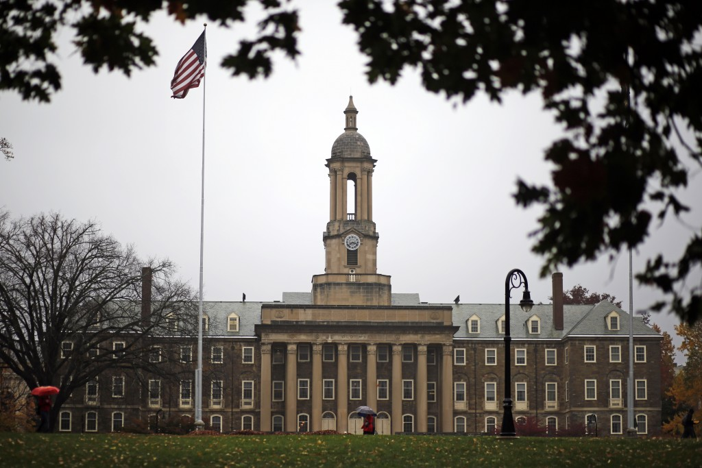 In this Oct. 28, 2015 file photo, a Penn State student walks in the rain past Old Main on the Penn State main campus in State College, Pa.   Under a n...