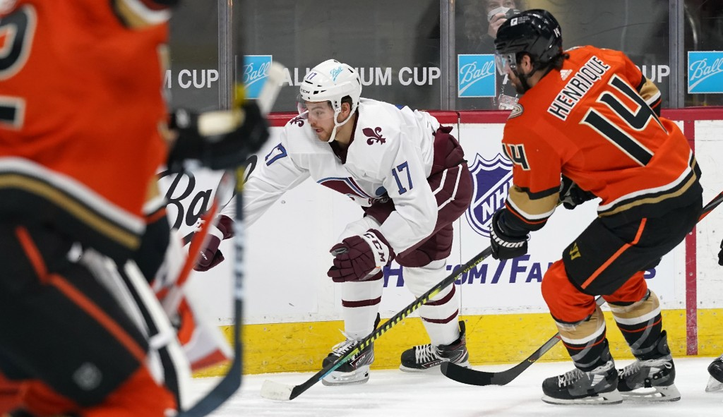 Colorado Avalanche center Tyson Jost, back left, reaches out to control the puck as Anaheim Ducks center Adam Henrique defends in the first period of ...