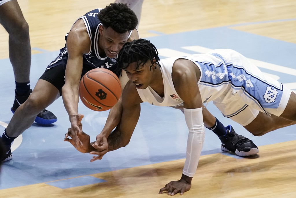 Duke forward Wendell Moore Jr. and North Carolina guard Caleb Love, right, struggle for a loose ball during the first half of an NCAA college basketba...