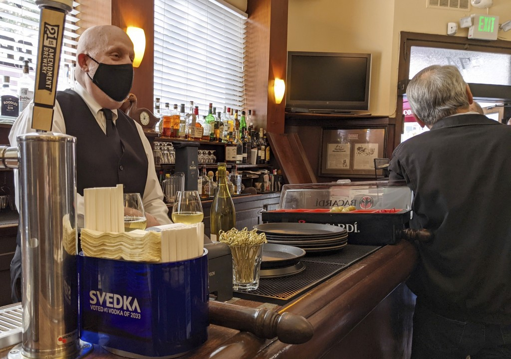 Bartender Dino Keres prepares drinks at Sam's Grill in San Francisco on Thursday, March 4, 2021.  As more states lift mask mandates and ease restricti...