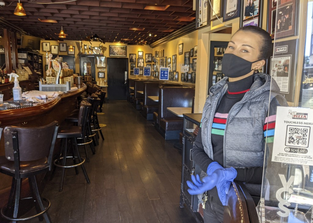 Ro Hart, an assistant general manager and hostess at Tony's Pizza Napoletana in San Francisco stands in front of a totally empty indoors seating area ...