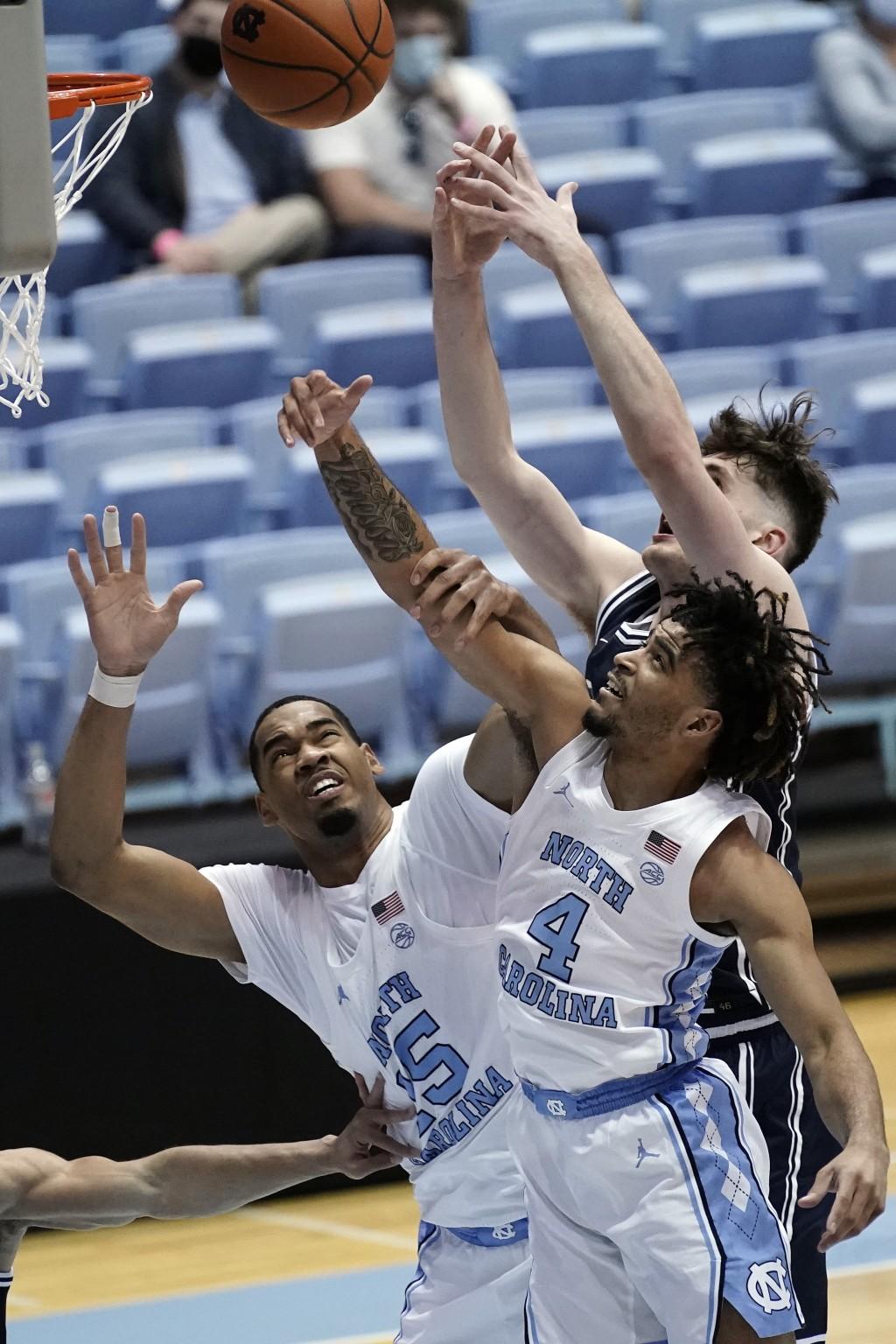 North Carolina forward Garrison Brooks (15) and guard R.J. Davis (4) reach for a rebound against Duke forward Matthew Hurt during the second half of a...