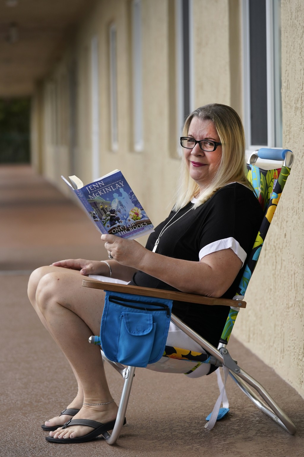 Kelly Vaiman poses for a photo along a walkway to her home where she likes to sit and read, Friday, Feb. 19, 2021, in Boynton Beach, Fla. Vaiman is an...