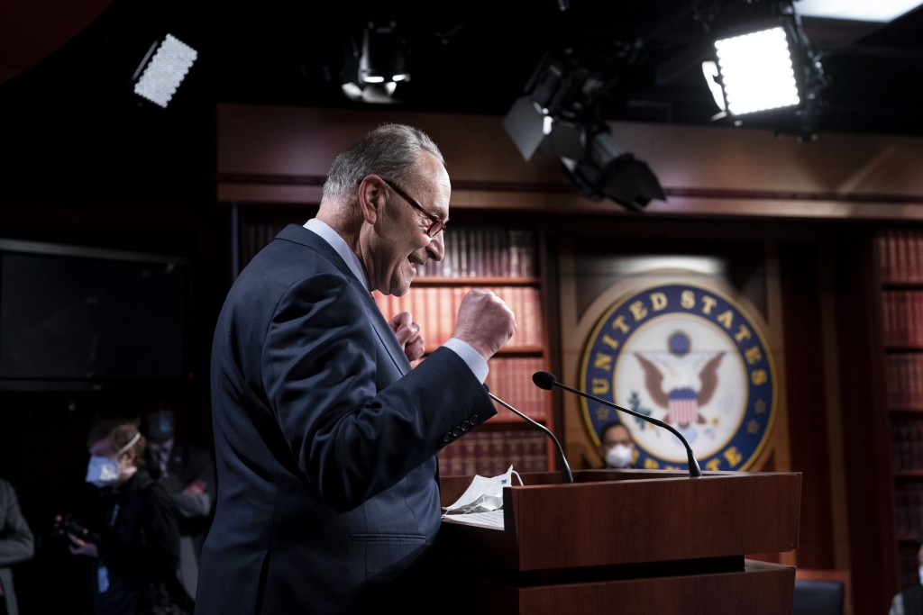 Senate Majority Leader Chuck Schumer, D-N.Y., praises his Democratic Caucus at a news conference just after the Senate narrowly approved a $1.9 trilli...