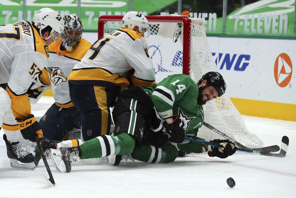 Dallas Stars left wing Jamie Benn (14) gets knocked to the ice by Nashville Predators defenseman Mattias Ekholm (14) while trying to score in the seco...