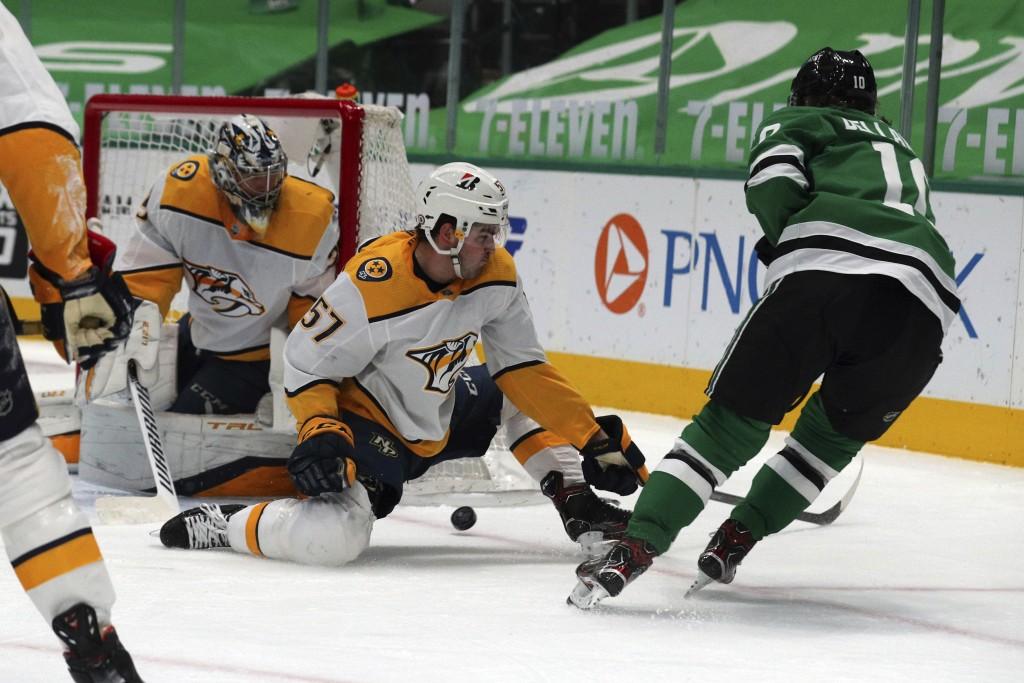Nashville Predators goaltender Pekka Rinne (35) and defenseman Dante Fabbro (57) defend against a shot by Dallas Stars center Ty Dellandrea (10) in th...