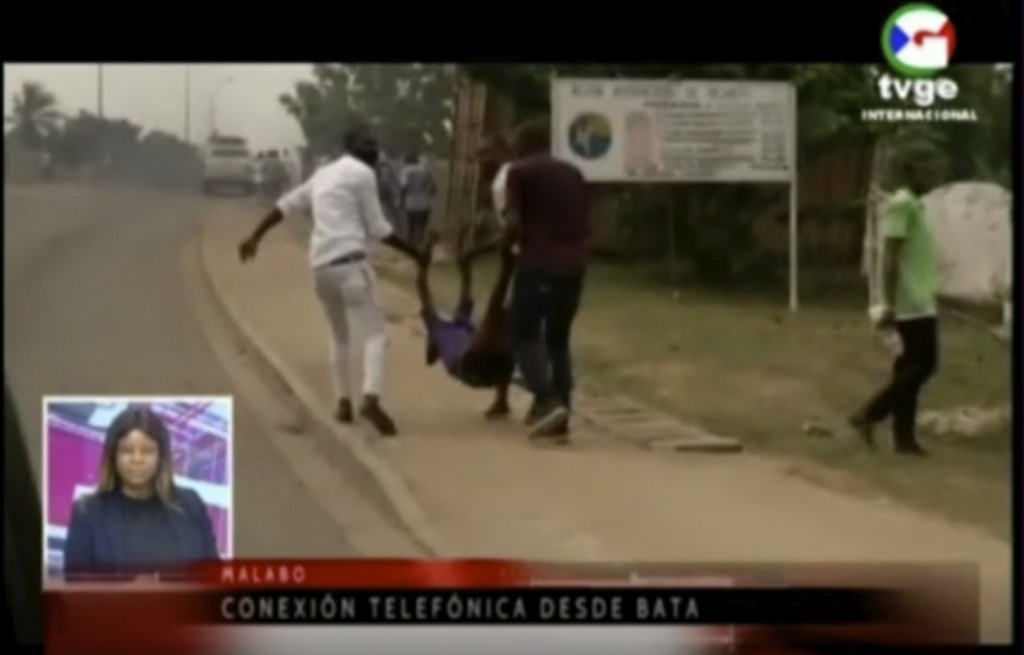 This TVGE image made from video shows people carrying a victim away after a blast site at a military barracks in Bata, Equatorial Guinea, Sunday, Marc...