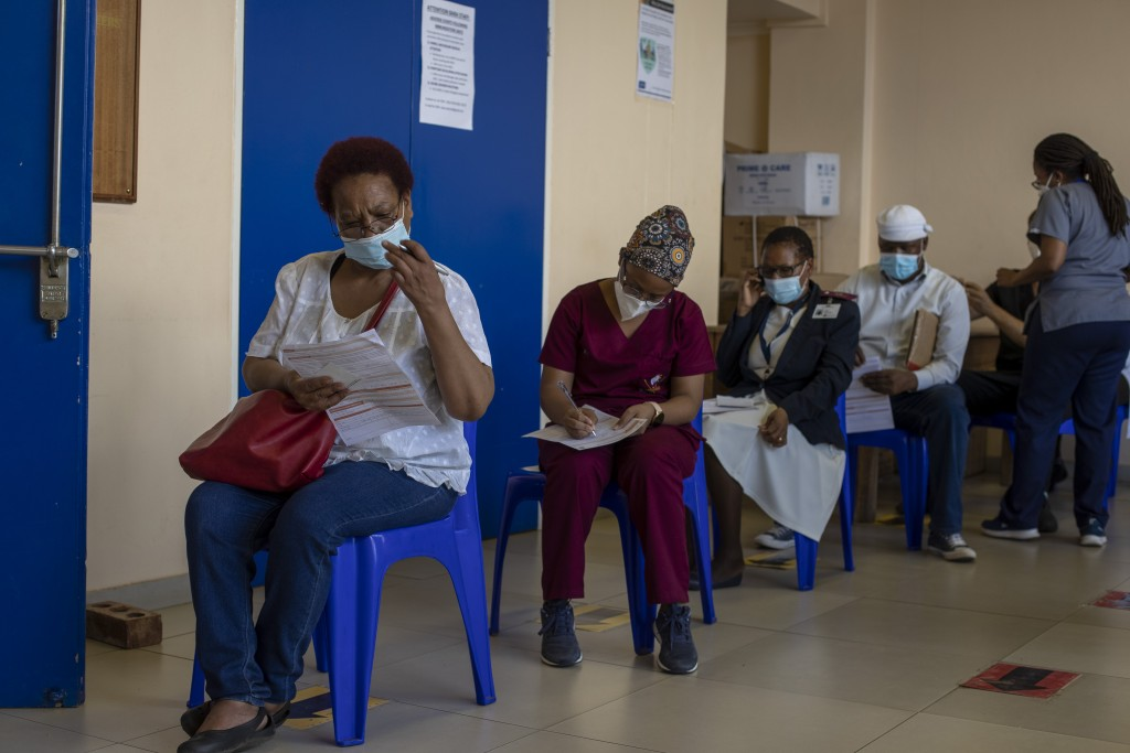Maggie Sedidi, left, a 59-year-old nurse at Soweto's Chris Hani Baragwanath hospital, reads a medical questioner before receiving her dose of the John...