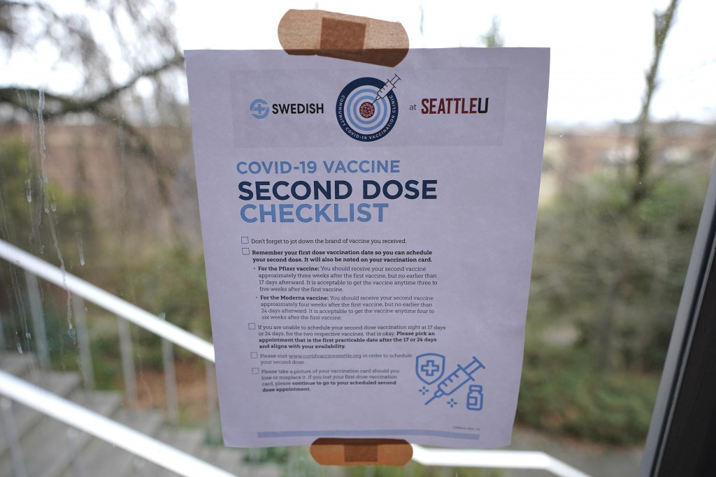 A checklist for people receiving the second dose of the Moderna or Pfizer COVID-19 vaccines is held to a window with adhesive bandages at a mass vacci...