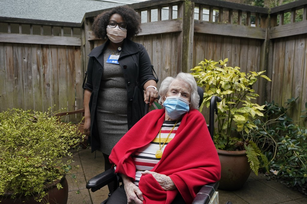 Sangu Kande, left, a nurse at Queen Anne Healthcare, a skilled nursing and rehabilitation facility in Seattle, poses for a photo, Friday, March 5, 202...