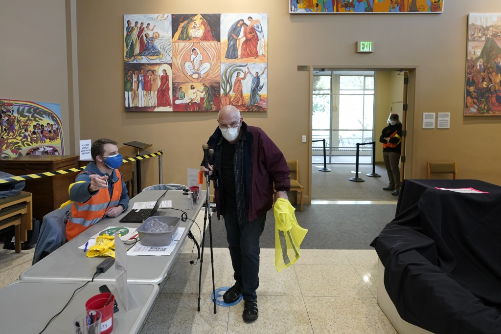 Volunteer worker Art Pasette checks in for his shift as a volunteer worker at a mass vaccination clinic at Seattle University, Friday, Feb. 26, 2021, ...