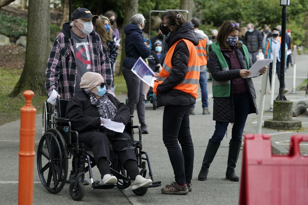 Wearing colored vests, volunteer workers talk with people in line for their appointments at a mass vaccination clinic at Seattle University, Friday, F...
