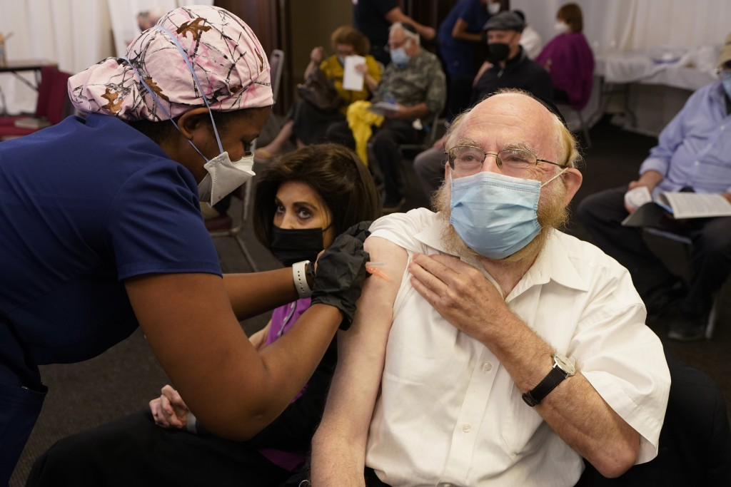 Ethel Schwartz, 71, watches as nurse Tiffany Hill prepares to administer the second dose of the Moderna COVID-19 vaccine to her husband Hyman Schwartz...