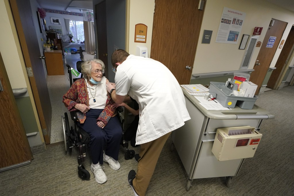 FILE - In this Jan. 8, 2021, file photo, Jean Allen, 96, left, receives the first shot of the Pfizer vaccination for COVID-19, from a Walgreens Pharma...