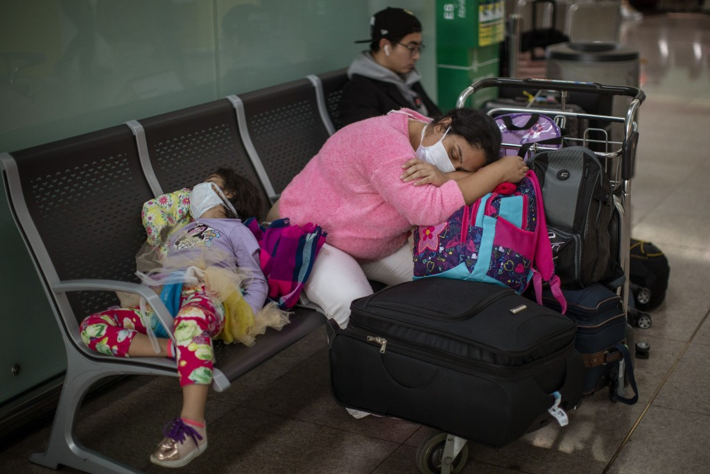 FILE - In this March 12, 2020, file photo, passengers rest at the Barcelona airport, Spain. President Donald Trump, who had downplayed the coronavirus...