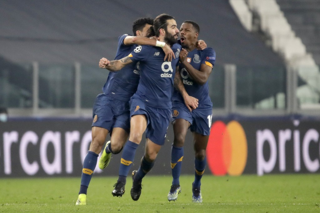 Porto's Sergio Oliveira, center, celebrates after scoring his side's second goal during the Champions League, round of 16, second leg, soccer match be...