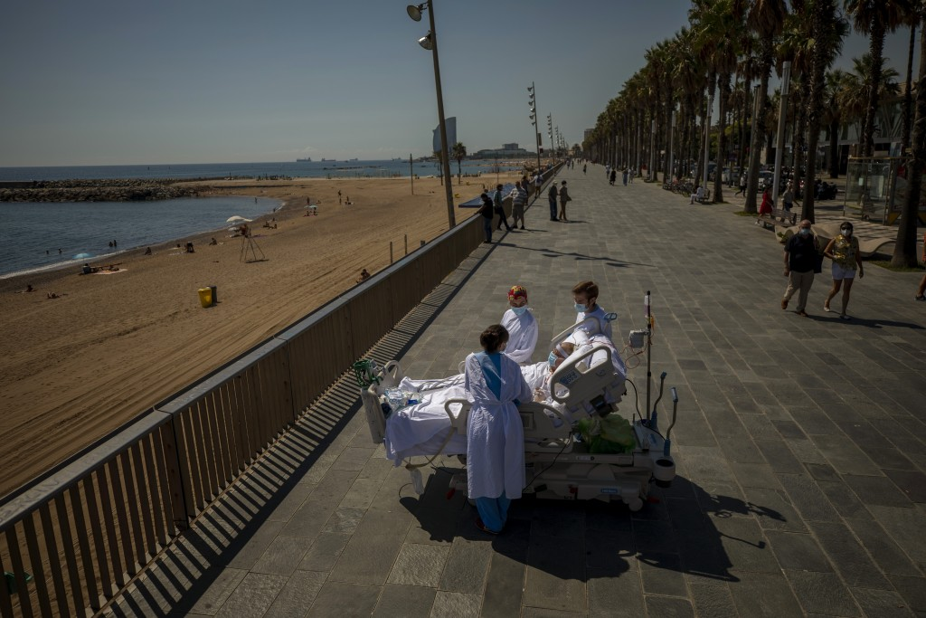 FILE - In this Sept. 4, 2020, file photo, Francisco Espana, 60, is surrounded by members of his medical team as he looks at the Mediterranean sea from...