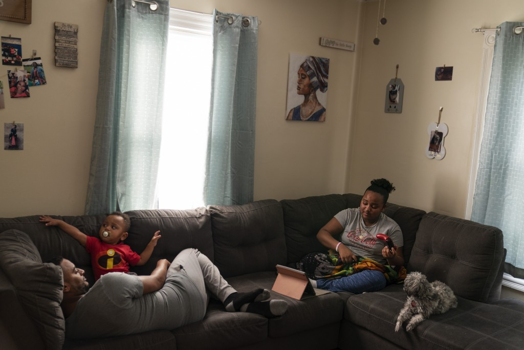 Darelyn Maldonado, 12, right, sits on the couch with her dog, Lisa, stepfather, Steven Depina, left, and 16-month-old brother, Elijah, at their home i...