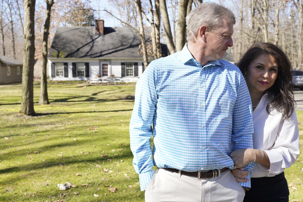 Matt Moorhead, left, looks at his wife, Alyson, as they pose for a photo outside their home, Tuesday, March 2, 2021, in Warren, Ohio. When General Mot...