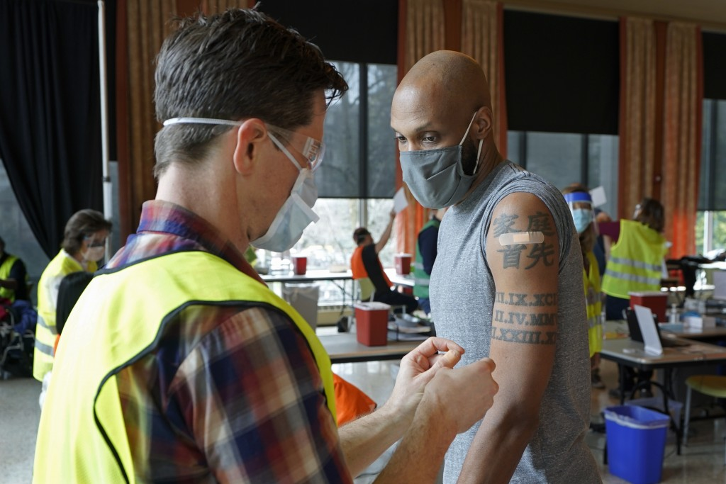 Shawn Brown, right, receives the second does of the Moderna COVID-19 vaccine from a volunteer worker at left, at a mass vaccination clinic at Seattle ...