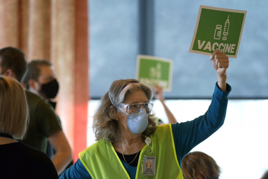 Sally Avenson, a nurse working as a volunteer at a mass vaccination clinic at Seattle University, holds up a sign to indicate she needs more doses of ...