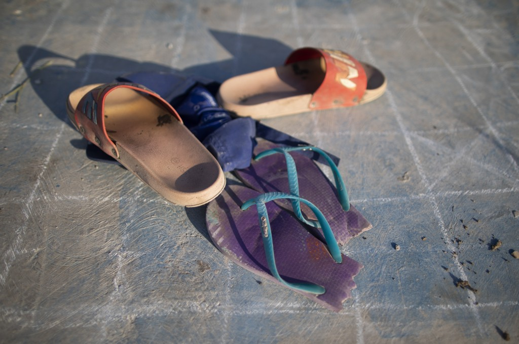 Children's broken sandals lay on a court as they play near the Pavia garbage dump, where their families rummage through garbage in search of valuable ...