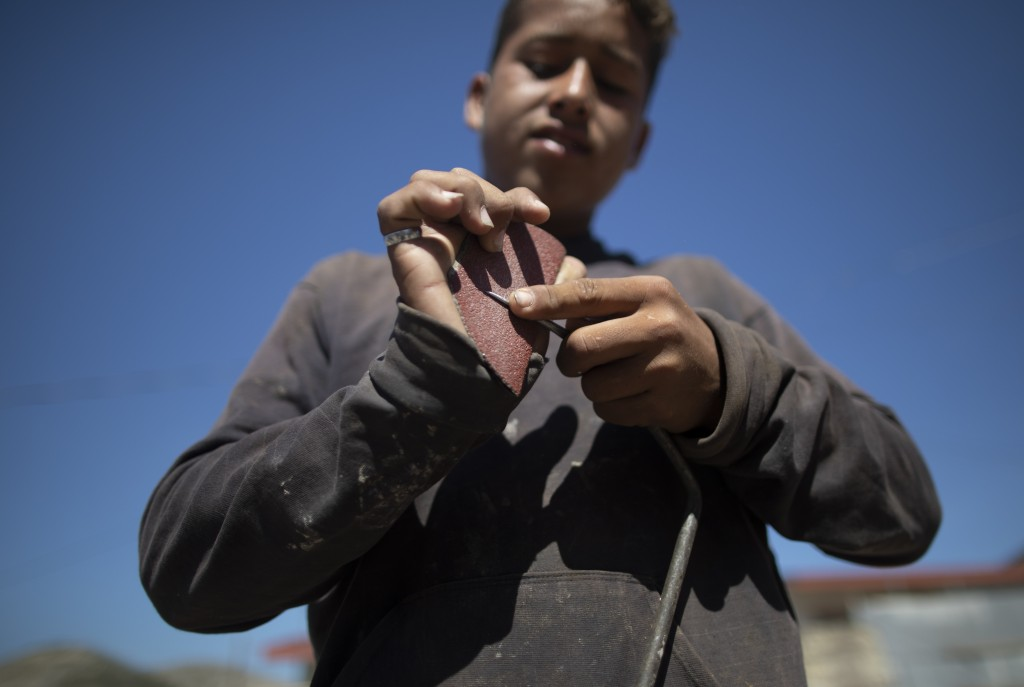 Ronaikel Brito sharpens the tip of a spike to use at the Pavia garbage dump on the outskirts of Barquisimeto, Venezuela, Wednesday, March 3, 2021. Bri...