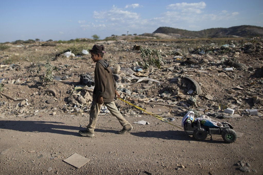 A boy pulls the remains of a toy car through the Pavia garbage dump where he searches for valuable items to resell on the outskirts of Barquisimeto, V...
