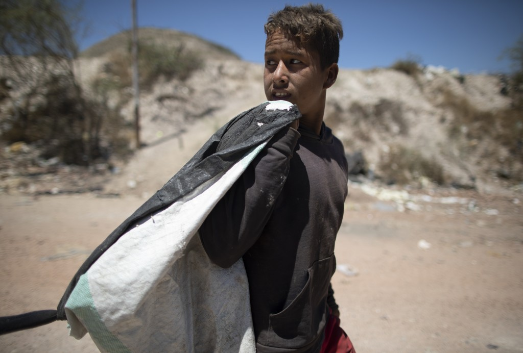 Ronaikel Brito walks home with a sack of things he collected from the Pavia garbage dump that he can sell, on the outskirts of in Barquisimeto, Venezu...