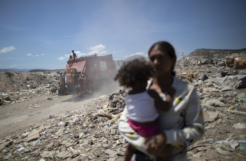 Youths looking for valuable items in the trash to resell ride on the back of a garbage truck entering the Pavia garbage dump on the outskirts of Barqu...