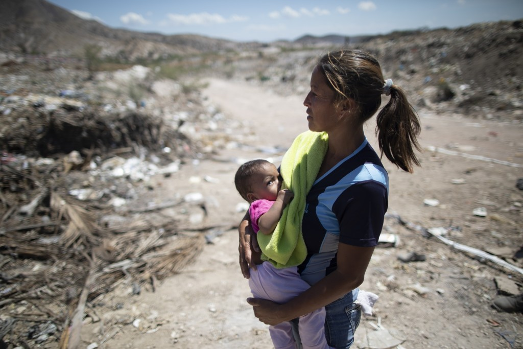 Marbelis Brito holds her 7-month daughter Antonela at the Pavia garbage dump where her family searches for valuable items to sell on the outskirts of ...