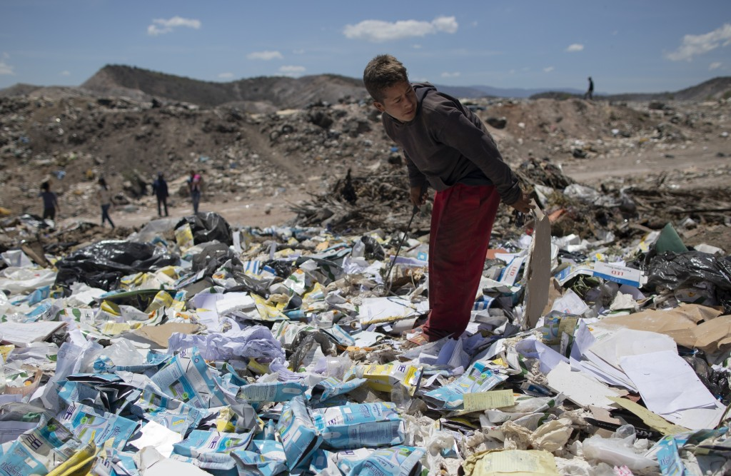 Ronaikel Brito, 16, rummages through empty milk cartons at the Pavia garbage dump on the outskirts of Barquisimeto, Venezuela, Wednesday, March 3, 202...