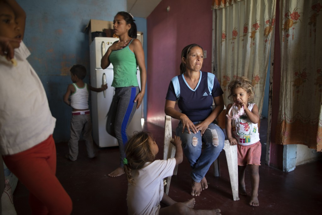 Marbelis Brito is surrounded by some of her eight children after giving a TV interview at her home near the Pavia garbage dump where three generations...