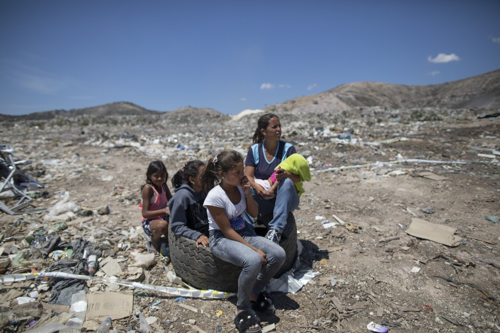 Marbelis Brito holds her 7-month-old daughter Antonela as she sits with her daughters while her teenage son Ronaikel searches for valuable items they ...