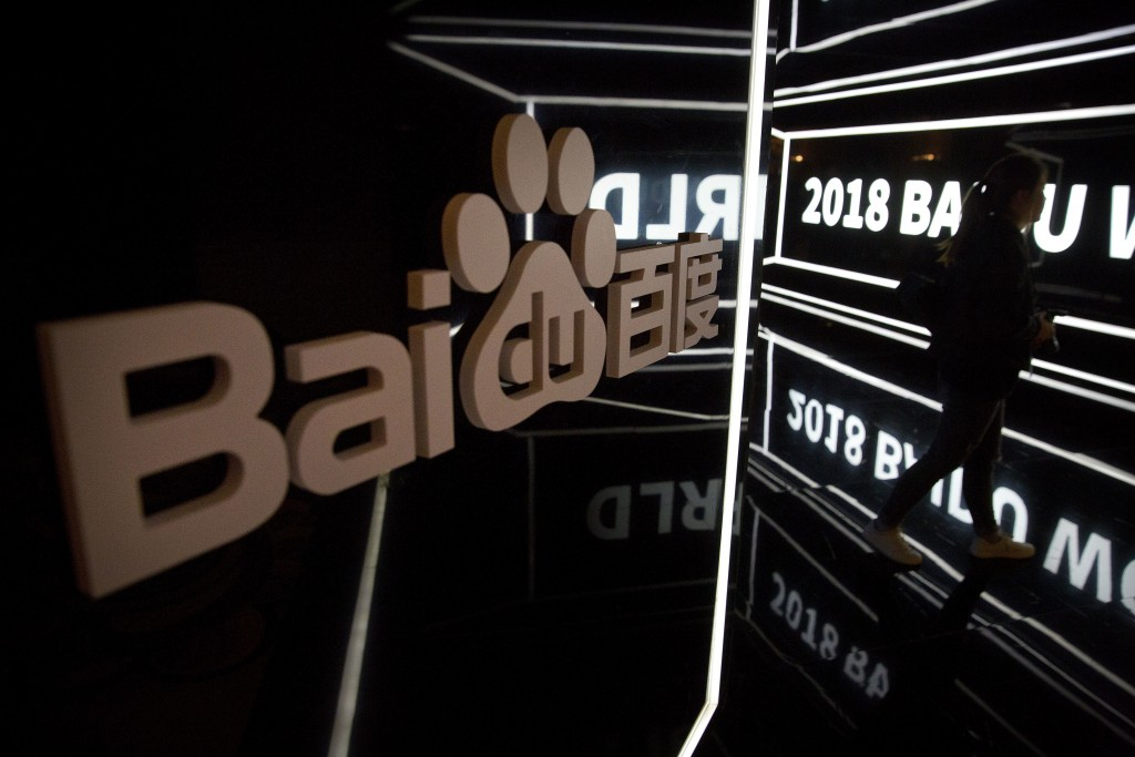 FILE - In this Nov. 1, 2018, file photo, an attendee walks past a display at the 2018 Baidu World conference in Beijing. China's market regulator said...