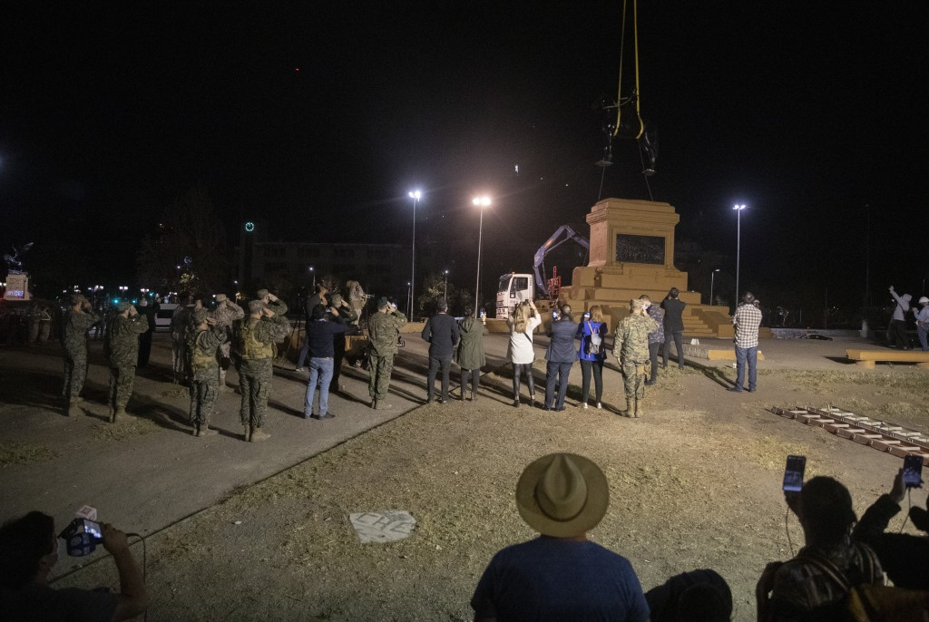 Soldiers salute as they stand guard while a statue of General Manuel Baquedano, a Chilean military officer and politician, is removed for restoration ...