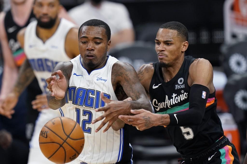 Orlando Magic forward Gary Clark (12) and San Antonio Spurs guard Dejounte Murray (5) scramble for the ball during the second half of an NBA basketbal...