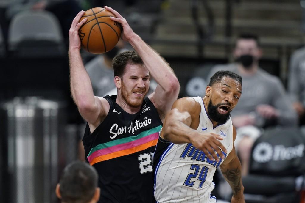 San Antonio Spurs center Jakob Poeltl (25) pulls down a rebound over Orlando Magic center Khem Birch (24) during the first half of an NBA basketball g...