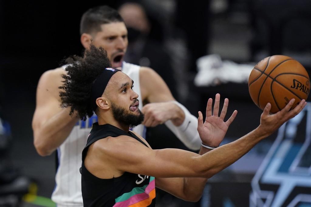 San Antonio Spurs guard Derrick White (4) drives past Orlando Magic center Nikola Vucevic (9) during the first half of an NBA basketball game in San A...