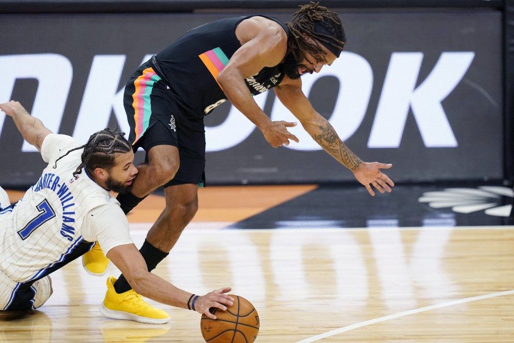 Orlando Magic guard Michael Carter-Williams (7) and San Antonio Spurs guard Patty Mills (8) chase a loose ball during the first half of an NBA basketb...